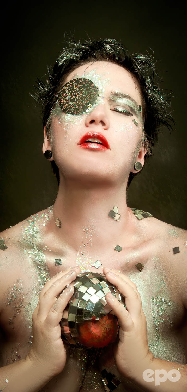 Woman in glitter makeup and eyepatch holds a cracked discoball with a heart inside.