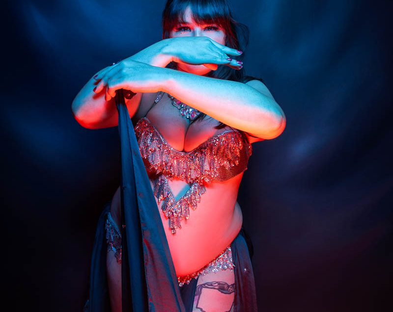 Dancer lit in blue and red poses in the dark